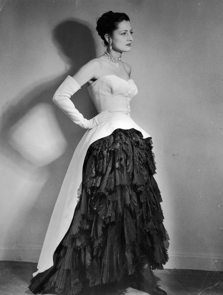 An evening dress designed by Cristobal Balenciaga with crisp white cotton pique cut away at the front to show a full skirt of soft black silk flounces. Original Publication: Picture Post - 5236 - Afternoon And Evening - pub. 1951
