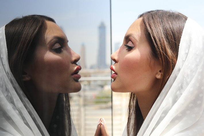 arabic woman looking into a mirror