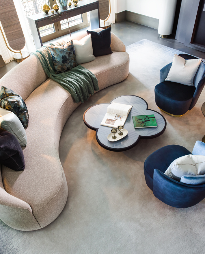 ariel view of a living room with a curved sofa and tub chairs in Clarges, Mayfair interior design by Elicyon