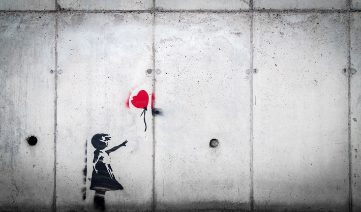 stencil of a little girl letting go of a red flower shaped balloon on a concrete wall - words of wisdom -forgiveness