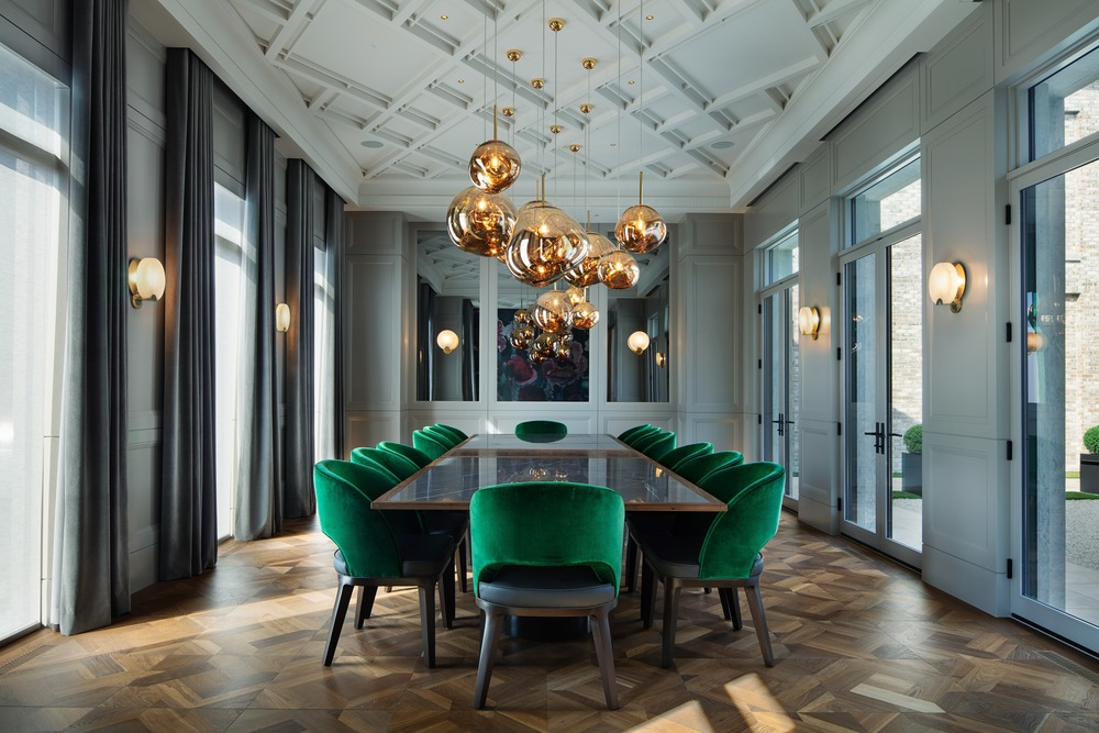 modern classic interior luxury dining room with emerald green chairs and tom dixon pendant lights by audax