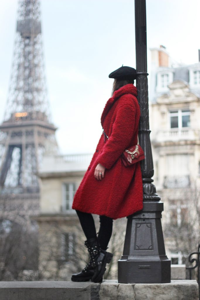 woman standing in a red coat with a designer bag looking at the Eiffel tower