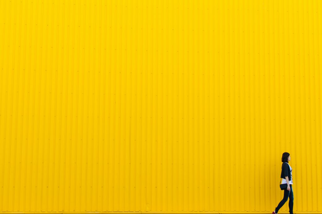woman walking in front of a yellow wall