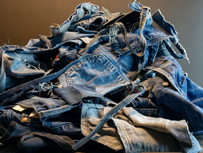 green is the new black - pile of blue jeans eco fashion sustainable living textile waste pollution