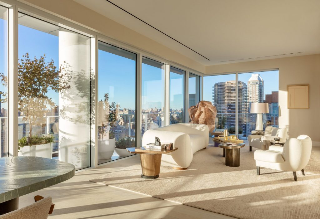 a cream living room design with lots of windows and a large terrace wrapping around it - nyc million-dollar listings