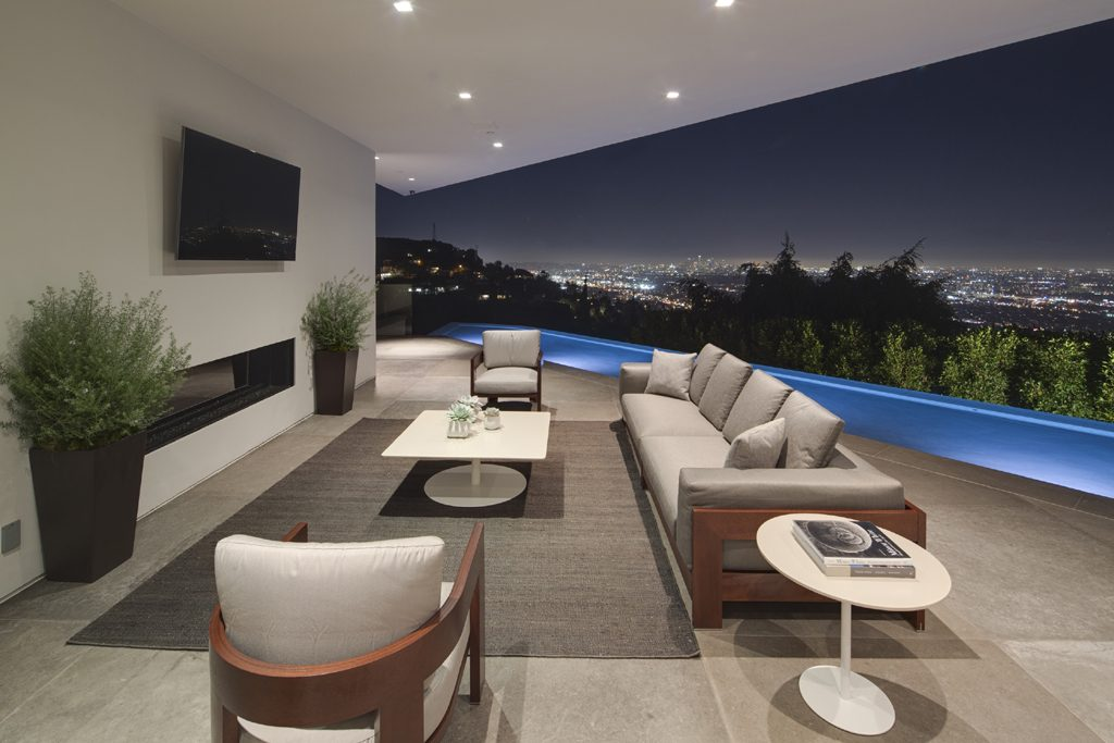 outdoor seating area with infinity pool overlooking los angeles