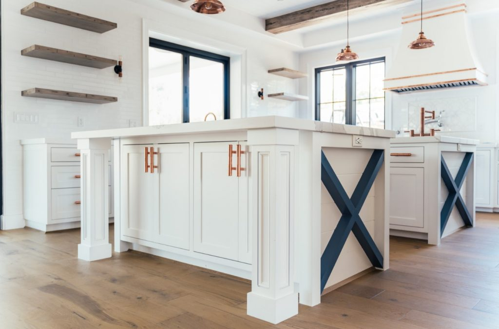 white kitchen with blue accents rustic elements and copper fixtures