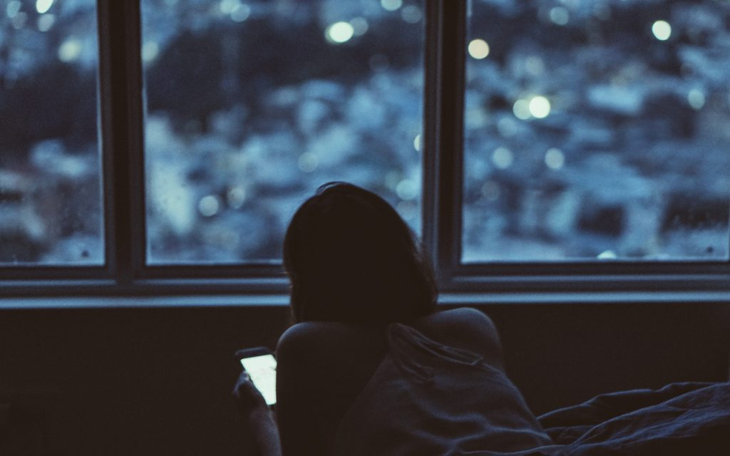 good night sleep - woman on cell phone in dark in bed
