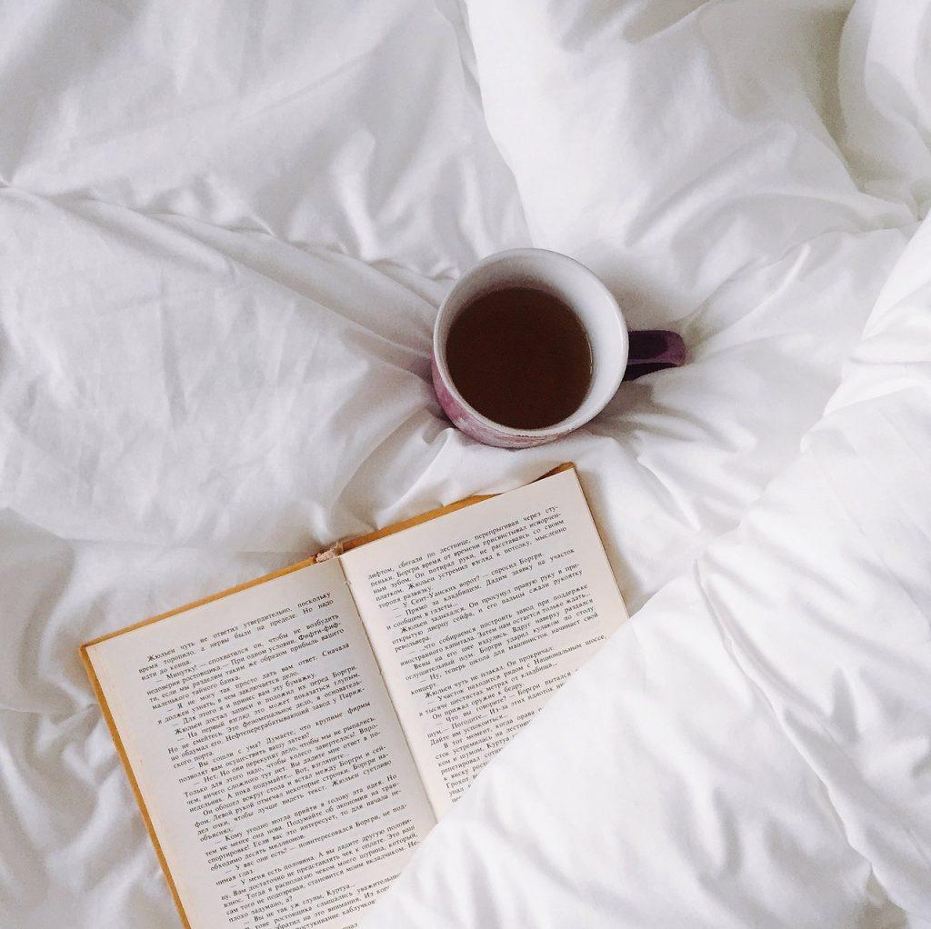 good night's sleep - white ceramic mug on white textile with open book