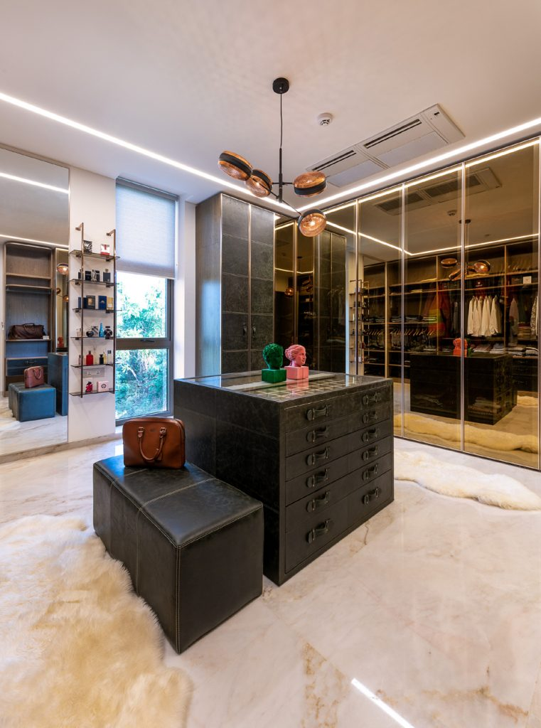 master closet with floor to ceiling mirrors and sheep skin rugs on marble floor