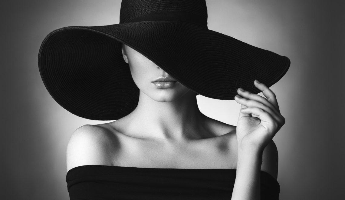 fashion forward luxury brands - Studio shot of young beautiful woman wearing hat on dark background