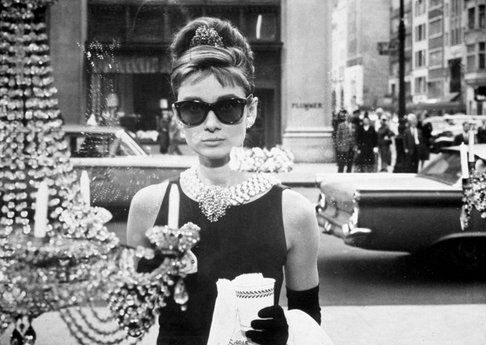 iconic fashion pieces 1961: Belgian-born actor Audrey Hepburn (1929 - 1993), as Holly Golightly, holds a cup and a paper bag while looking into one of the window displays at Tiffany's in a still from the film, 'Breakfast at Tiffany's,' directed by Blake Edwards. She wears sunglasses, a little black dress, long gloves and a tiara in her chignon. (Photo by Paramount Pictures/Getty Images)