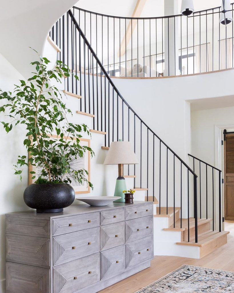 california chic foyer with a statement cabinet and iron railing and light wood floors