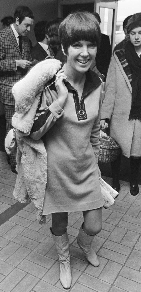 iconic fashion pieces Mary Quant wearing a mini dress of her own design, with a sheepskin coat and bag thrown over her shoulder, and wearing go-go boots 1966