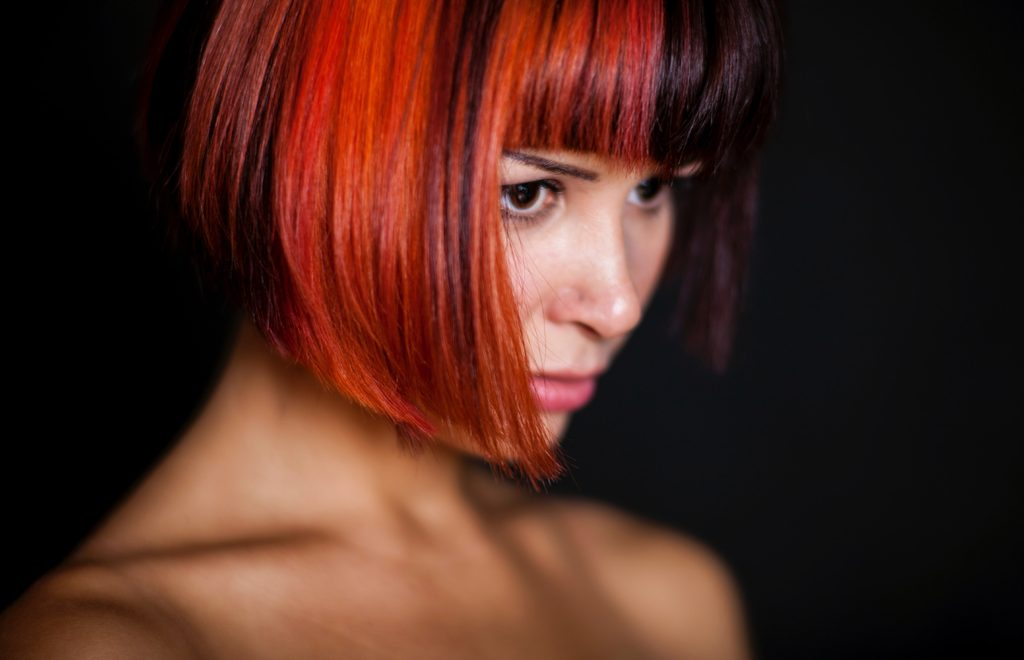 how to take care of your dyed hair - woman with bob hair style half red half black photo by engin akyurt-unsplash