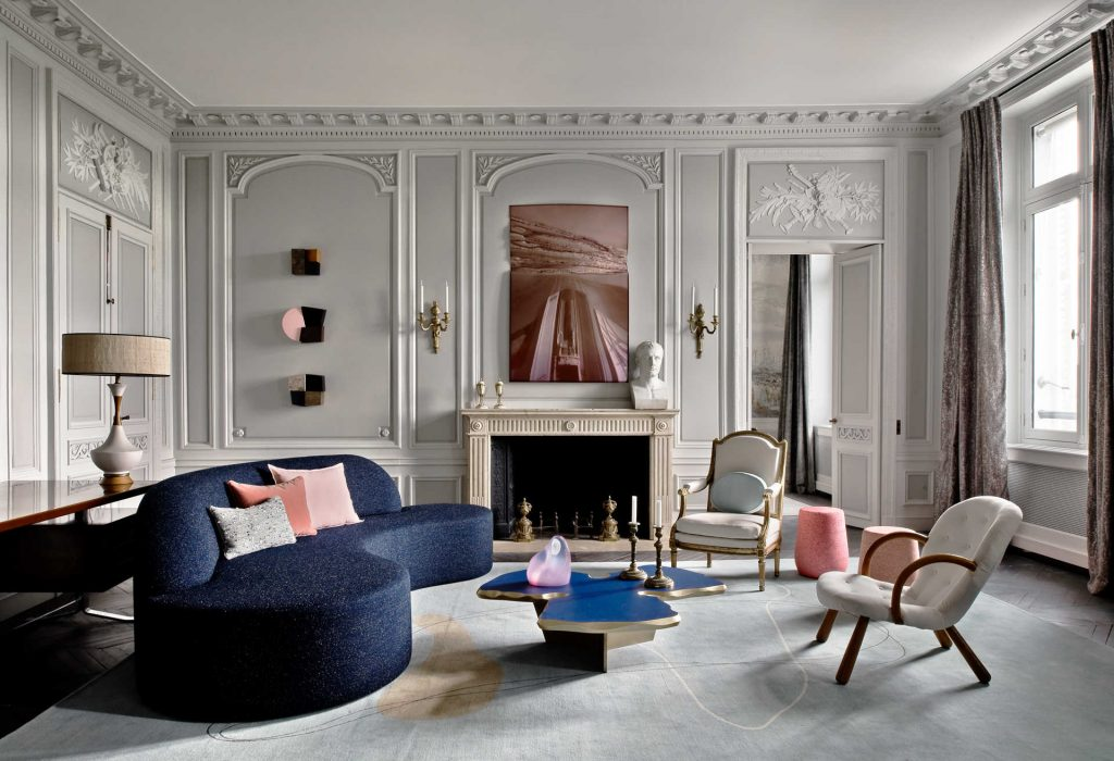Apartment rue de Rivoli Living room  Grey paneling color: river reflecting by Benjamin Moore Trim color: china white by Benjamin Moore Artwork (over the mantel): untitled colored varnish on mirror Perspex by Jerome Robbe Artwork (series to the left of the mantel): 3 vintage wall sculptures 1970 anonymous Sconces: Bronze Louis XVI Sofa: Bangkok blue sofa, Jean-Louis Deniot custom Cushions (on blue sofa): Lelievre et Pierre Frey Coffee table: Clover-shaped coffee table patinated brass with blue lacquered wood tray and gold leaf rim, Jean-Louis Deniot custom On the coffee table: Anonymous 1970 resin abstract sculpture and Louis XVI period candlesticks Rug: wool rug Diurne (custom made by JLD) Chair: Bergere armchair and upholstery fabric Louis XVI attributed to Geroges Jacob Chair: Midcentury armchair and upholstery fabric, Clam chair Philp Arctander Pink side tables: Lightweight porcelain collection side table Djim berger Table lamp: 1950s table lamp from LA unknown Bust (on mantel): Bust of napoleon in marble 19th century, Canova Paneling: Louis XVI all orginal in this section Jean-Louis Deniot Mantel: Louis XVI Decorative motif (over doorway and in arches): Louis XVI - music theme Molding style: Louis XVI Flooring: Parqueterie - Point D'Hongrie