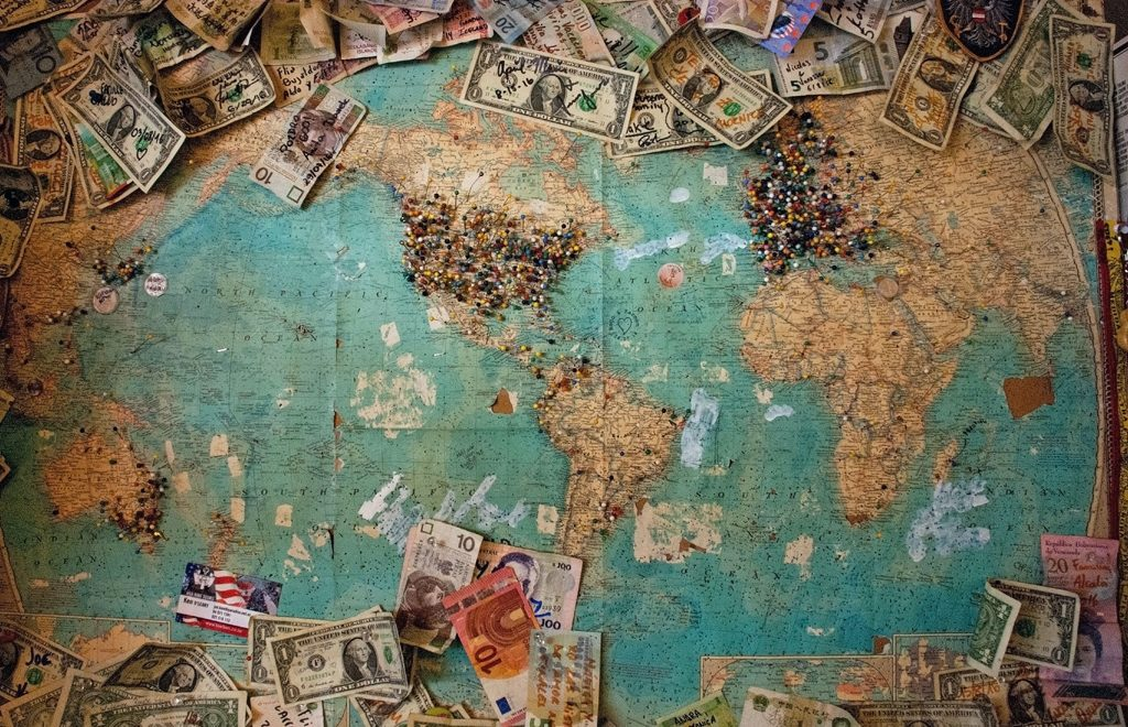 tips for saving money during pandemic - money on a world map - photo by christine roy unplash