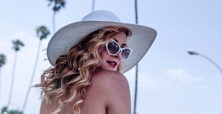 beautiful woman staying young in white sunglasses and hat