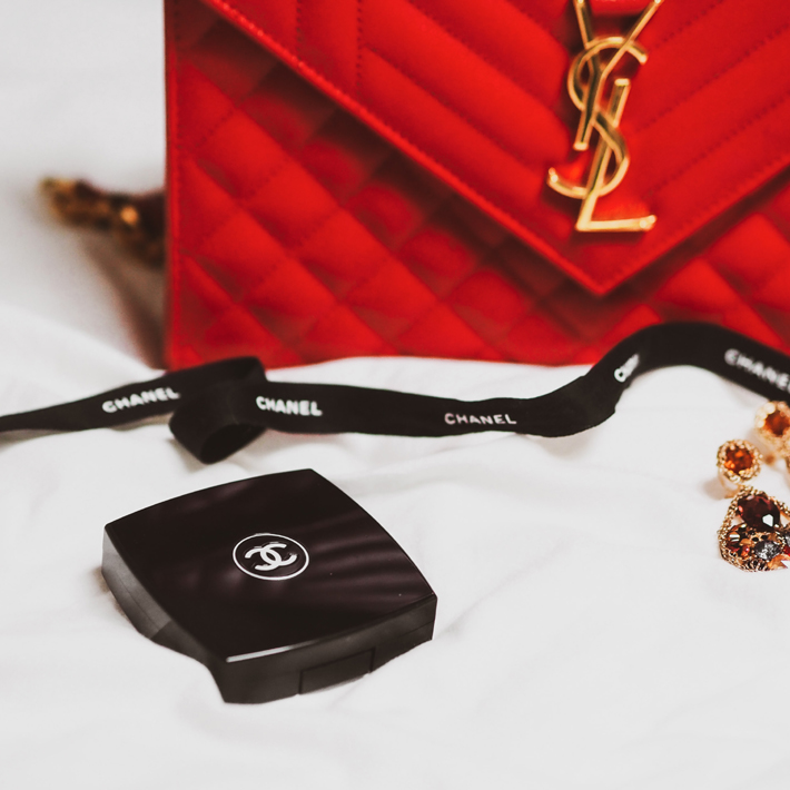 red ysl purse, chanel make up and jewelry photo by laura chouette