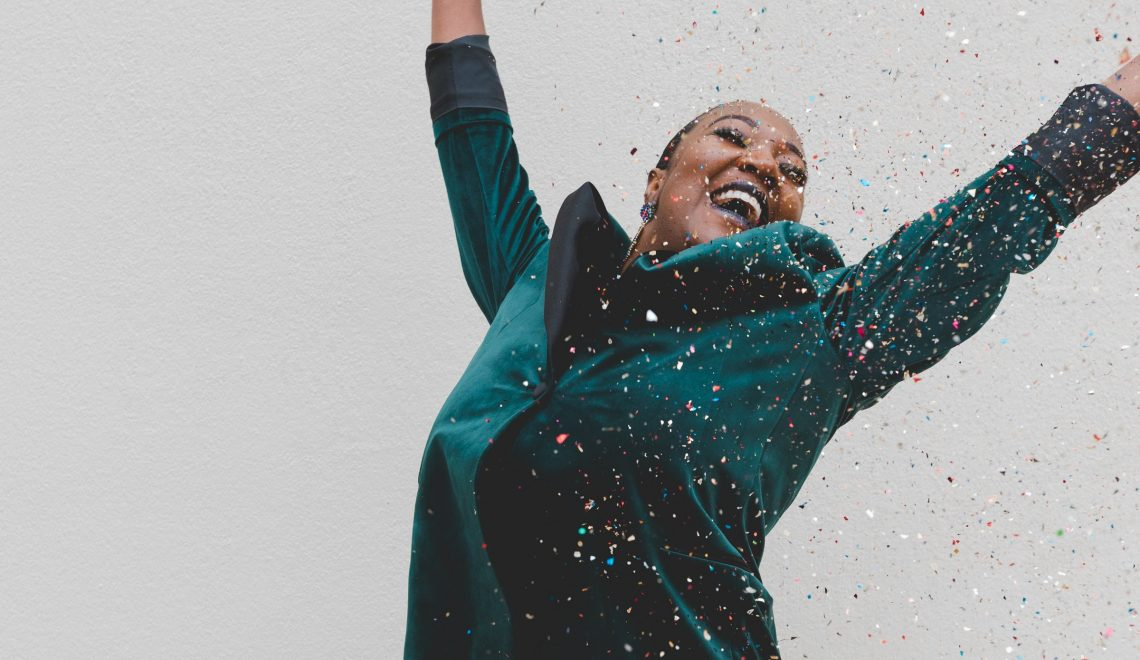 healthy new year intentions resolutions celebrate woman throwing confetti