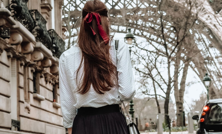 Fashion style rules french women follow woman with red ribbon in hair by eiffel tower