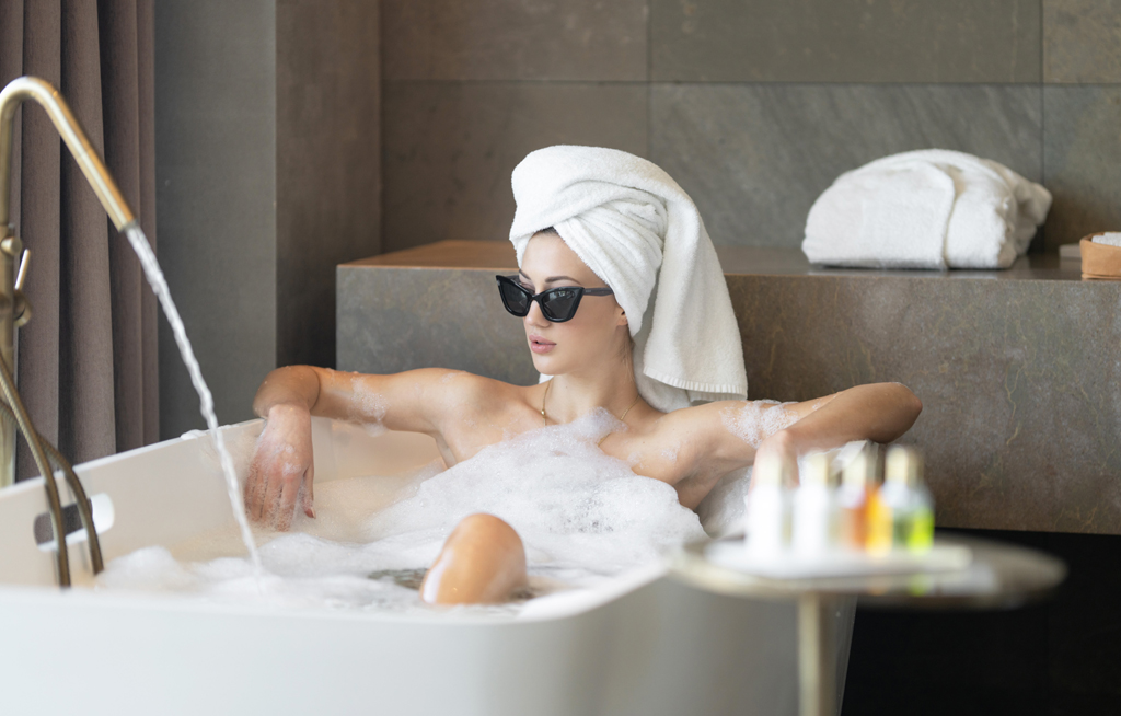 at home spa day crystalweed cannabis unsplash woman in tub wearing sunglasses