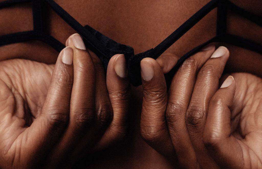 woman undoing black bra back womanizer wow tech unsplash