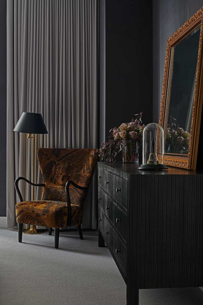 interior design detail of wing chair and dresser gold and black modern victorian