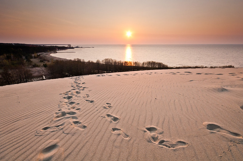 Early morning sun casting its rays on the dune of Parnidis and Nida harbor, Lithuania (Photo by Vaidotas Mišeikis)