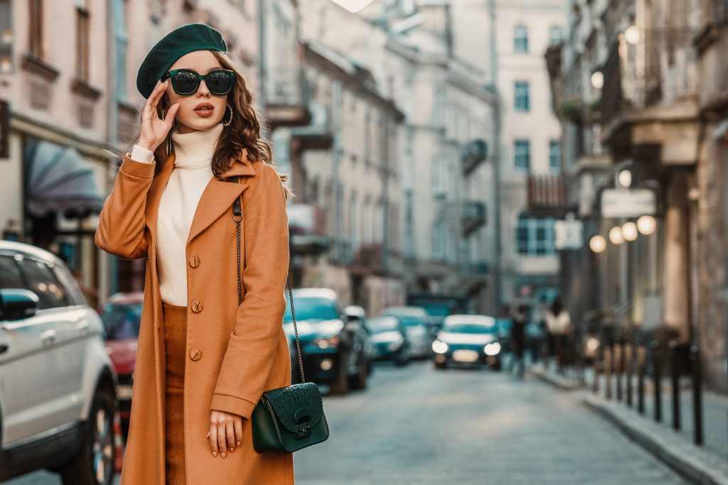 how to accessorize with accent colors woman wearing green sunglasses, hat and purse