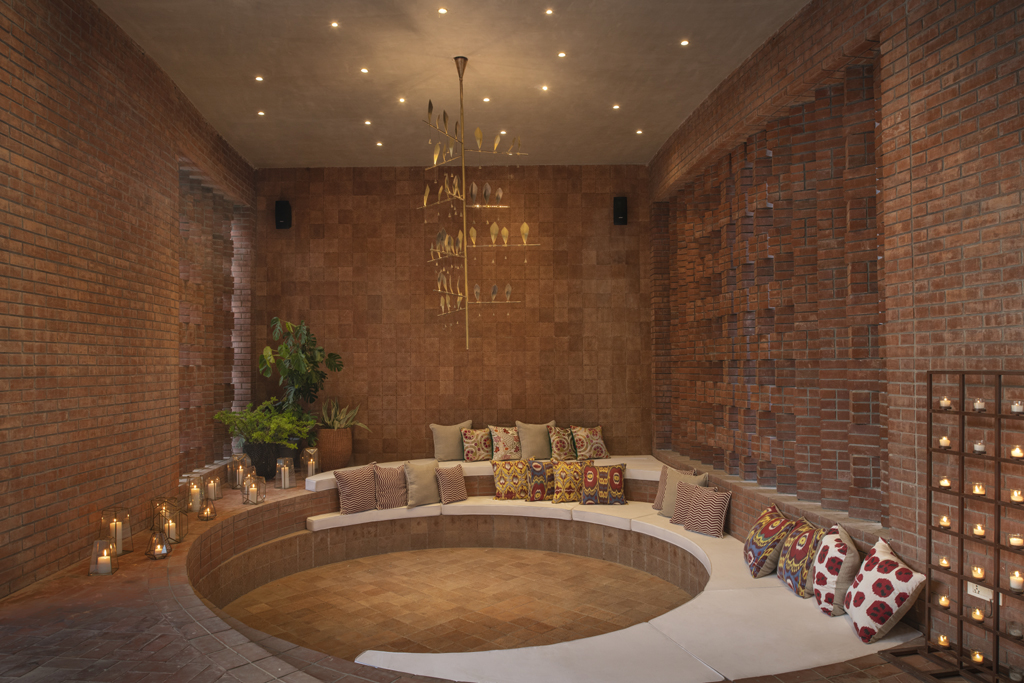 Farm House in India designed by Shalini Misra brick round set-in sofa seating area outdoor living room lounge new dheli