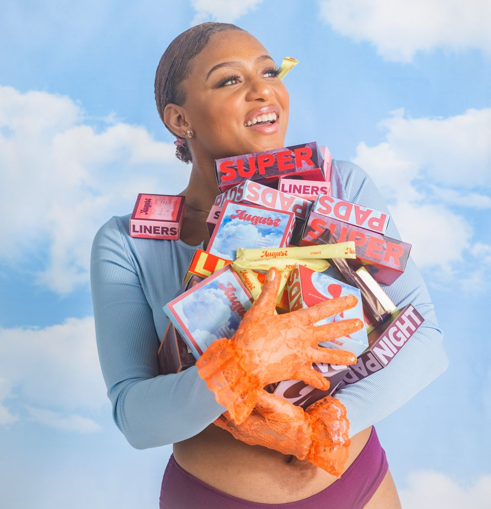 august sustainable period care products being held by a woman