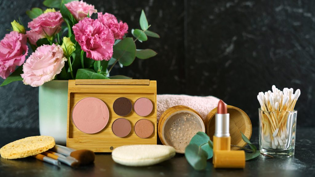 The vegan red lipstick, cruelty free blush palette, fluffy brushes, and setting powder are behind a black marble background with beautiful pink flowers next to them.