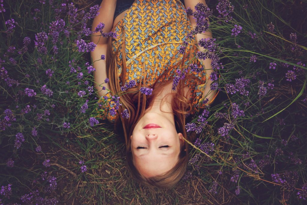 Girl laying in flowers meditating, peaceful Photo by Amy Treasure