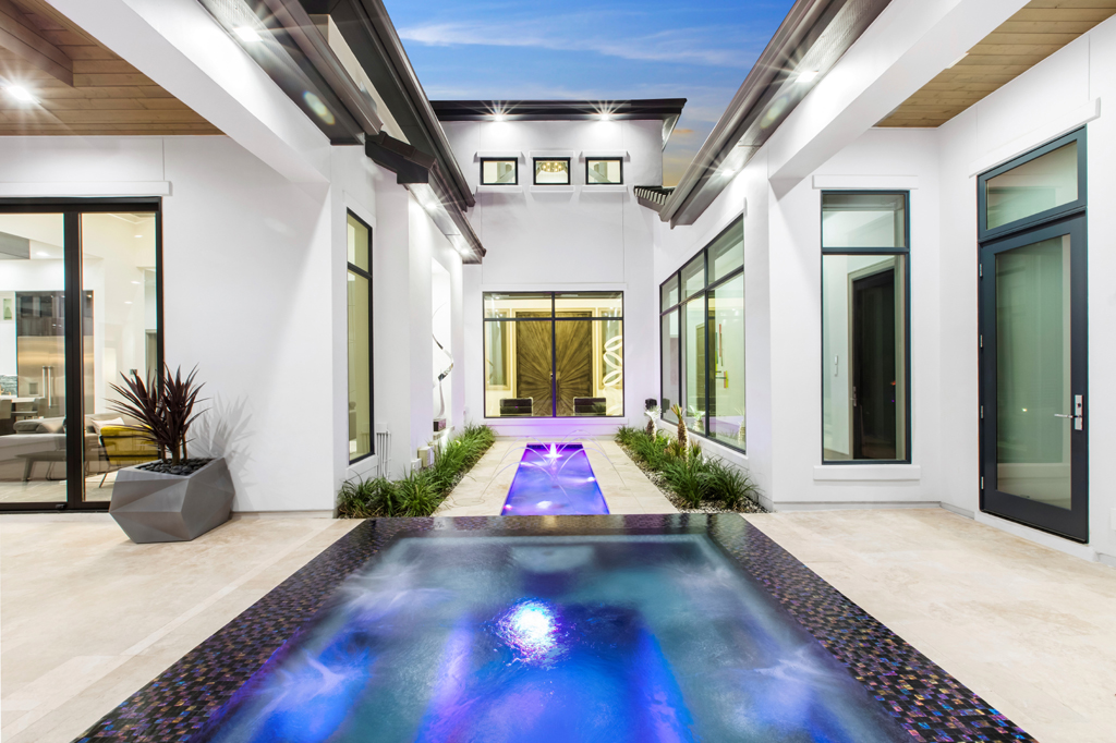 exterior of luxury home with water feature by jaimie anand - photo alberto vasquez