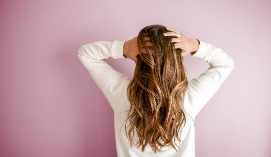 are clip-in or tape hair extensions better woman running her fingers through her hair
