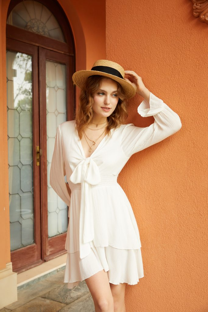 beautiful woman wearing a white longsleeve dress with a fashionable straw hat in front of an orange stucco wall