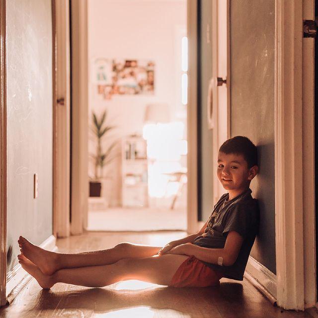young boy sitting in hallway Photo by Barbara Larson