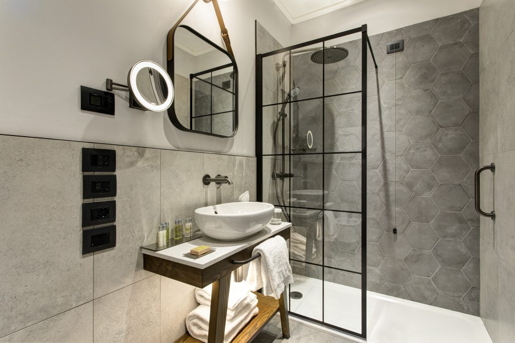 Concrete tiles add rustic glamour to this bathroom at Roma Monti Hotel designed by THDP (Photo by Janos Grapov)