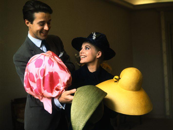 Italian star Virna Lisi trying on hats with the help of then Bergdorf Goodman milliner designer Halston, 1964